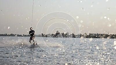 Ο Wakeboard κάνει βόλτες πάνω στο πλοίο πίσω από το μοτοποδήλατο και κρατά λαβή με σχοινί κατά τη διάρκεια του καλοκαιριού στο πο απόθεμα βίντεο