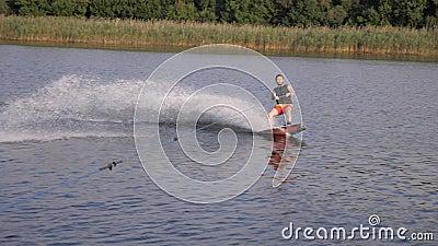 Ο Wakeboard κρατά λαβή με σχοινιά και κάνει βόλτες στο ποτάμι σε αργή κίνηση με το νερό να εκτοξεύεται στο φόντο των αλεπούδων φιλμ μικρού μήκους