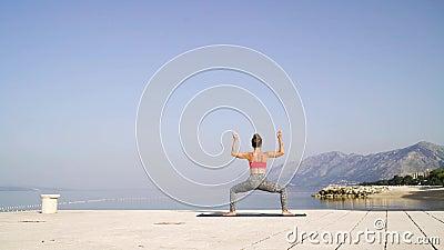 Πίσω άποψη της γυναίκας που κάνει τη γιόγκα στην παραλία με τα βουνά και τον ουρανό στο υπόβαθρο απόθεμα βίντεο