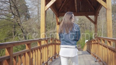 Πίσω άποψη της νέας γυναίκας γοητείας που περπατά αργά στην ξύλινη γέφυρα που κοιτάζει γύρω Ο θαυμασμός κοριτσιών όμορφου απόθεμα βίντεο