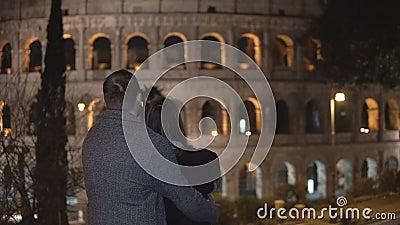 Πίσω άποψη του νεαρού άνδρα και της γυναίκας που στέκονται κοντά στο Colosseum στη Ρώμη, την Ιταλία και το αγκάλιασμα από κοινού φιλμ μικρού μήκους