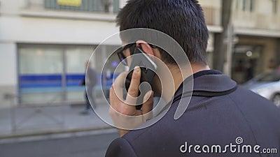 Πίσω άποψη του ψηλού ατόμου που συζητά συναισθηματικά τα ζητήματα τηλεφωνικώς στην οδό πόλεων απόθεμα βίντεο