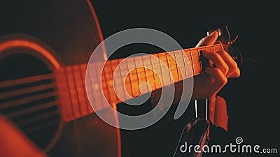 Παίζοντας μια ηχητική κιθάρα με κόκκινο οπισθοφωτισμό και μαύρο φόντο απόθεμα βίντεο