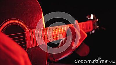 Παίζοντας μια ηχητική κιθάρα με κόκκινο οπισθοφωτισμό και μαύρο φόντο φιλμ μικρού μήκους