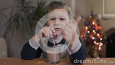 Παιδί που πίνει ένα νόστιμο ποτό μέσω ενός αχύρου στο σπίτι απόθεμα βίντεο