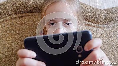 Παιχνίδια κοριτσιών εφήβων στο τηλέφωνο καθμένος στον καναπέ φιλμ μικρού μήκους