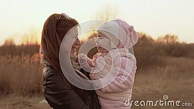 Παιχνίδια Mom με την κόρη και την κατοχή της διασκέδασης ενάντια του ουρανού ηλιοβασιλέματος απόθεμα βίντεο
