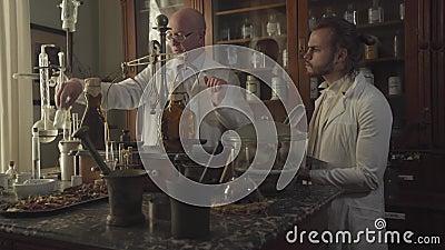 Παλαιός Καυκάσιος φαρμακοποιός που φοράει γυαλιά και δείχνει φιάλη με διαφανές υγρό σε νεαρό με λευκή ρόμπα Νέο φιλμ μικρού μήκους