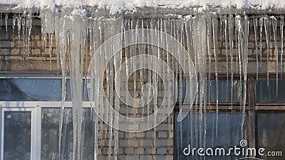 Παλαιό και νέο παράθυρο Ένας τεράστιος αριθμός των μεγάλων λειώνοντας παγακιών στη στέγη του σπιτιού το χειμώνα φιλμ μικρού μήκους