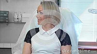 Πανέμορφη γυναίκα που χαμογελάει ενώ μιλάει στον αισθητικό της στην κλινική λουτρών απόθεμα βίντεο