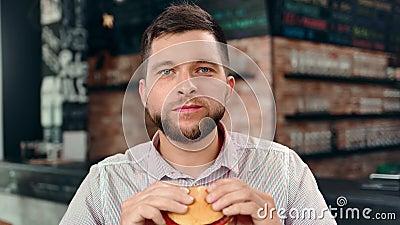Πεινασμένο γενειοφόρο νέο λεπτό άτομο που απολαμβάνει δαγκώνοντας νόστιμο burger που αισθάνεται την ευχαρίστηση που εξετάζει τη κ απόθεμα βίντεο