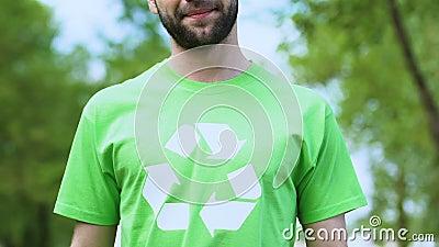Περήφανος άντρας με πράσινο μπλουζάκι με σύμβολο ανακύκλωσης χαμογελώντας στην κάμερα, την οικολογία απόθεμα βίντεο
