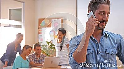 Περιστασιακός επιχειρηματίας που έχει το τηλεφώνημα με τους συναδέλφους του πίσω από τον απόθεμα βίντεο