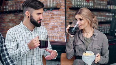 Περιστασιακός χαμογελαστός άνδρας και γυναίκα απολαμβάνουν άτυπη συνάντηση πίνοντας μπύρα τρώγοντας φαστ φουντ φιλμ μικρού μήκους