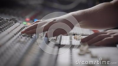 Πλάγια όψη που πυροβολείται ενός μουσικού που εργάζεται στον ήχο που αναμιγνύει την κονσόλα σε ένα στούντιο μουσικής απόθεμα βίντεο