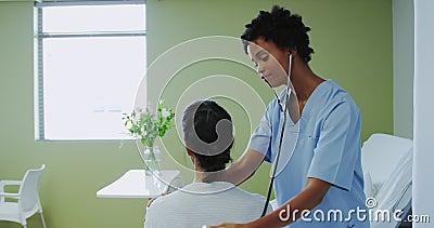 Πλαϊνή όψη της Αφρικανίδας αμερικανίδας γιατρού που εξετάζει γυναίκα ασθενή στο θάλαμο στο νοσοκομείο απόθεμα βίντεο