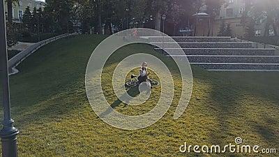 Ποδηλάτης γυναικών που βρίσκεται στην πράσινη χλόη στο πάρκο και που χρησιμοποιεί το κινητό τηλέφωνο απόθεμα βίντεο