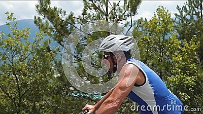 Ποδηλάτης ποδηλάτων ποδηλάτων που δουλεύει σκληρά και κινείται γρήγορα Ανώτερος αθλητής απόθεμα βίντεο