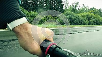 Ποδηλασία POV Το χέρι ενός ανθρώπου σε μια λαβή ποδηλάτου, ενώ ιππεύει κατά μήκος του αγροτικού δρόμου σε μια βροχερή μέρα απόθεμα βίντεο