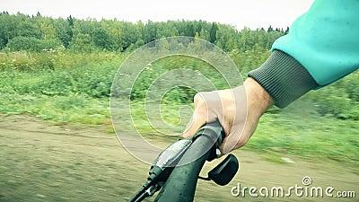 Ποδηλασία POV Χέρι ανθρώπου σε λαβή ποδηλάτου και ροδέλα, ενώ οδηγεί κατά μήκος του δασικού δρόμου σε μια βροχερή ημέρα απόθεμα βίντεο