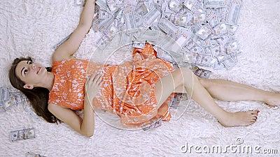Πολλά τραπεζογραμμάτια πετάνε στον αέρα πάνω σε ένα κορίτσι ξαπλωμένο σε λευκό κρεβάτι σε αργή κίνηση Τεράστιος πλούτος χρημάτων φιλμ μικρού μήκους