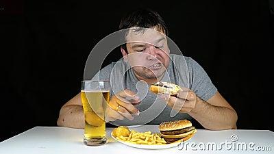 Πορτρέτο ενός άπληστου παχιού ατόμου που τρώει burger στο μαύρο υπόβαθρο φιλμ μικρού μήκους