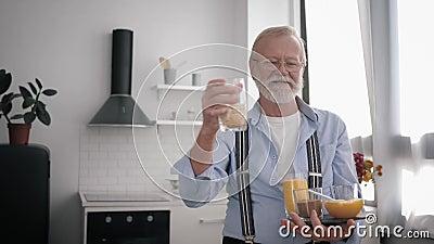 Πορτρέτο ενός ελκυστικού γέρου με μούσι και γυαλιά για όραση, μιλώντας για χρήσιμα δημητριακά για τη διατήρηση της υγείας απόθεμα βίντεο