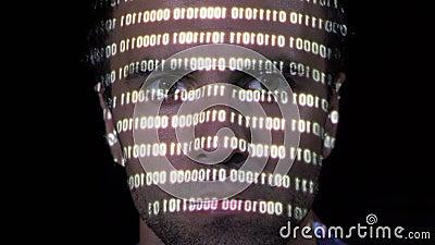 Πορτρέτο ενός νέου χάκερ που διαβάζει το δυαδικό κώδικα ransomware ενός επικίνδυνου ιού ενώ το στοιχείο προβάλλεται στο πρόσωπό τ φιλμ μικρού μήκους