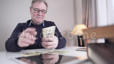 Πορτρέτο ενός πλούσιου Καυκάσου που μετρά μετρητά σε εσωτερικούς χώρους Χαμογελαστός ηλικιωμένος συνταξιούχος με γυαλιά φιλμ μικρού μήκους