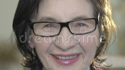 Πορτρέτο κινηματογραφήσεων σε πρώτο πλάνο του κοιτάγματος της ευτυχούς ώριμης γυναίκας στη κάμερα αργά φιλμ μικρού μήκους