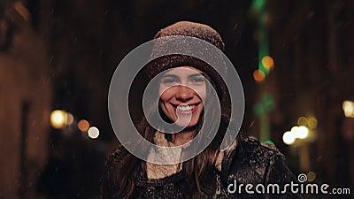 Πορτρέτο της νεαρής όμορφης κοπέλας με το χειμερινό καπέλο και τα γάντια που περπατούν στο χιόνι, δείχνοντας και χαμογελώντας απόθεμα βίντεο