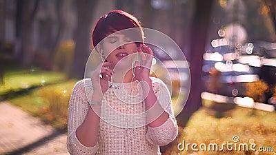 Πορτρέτο του νέου ρόδινος-μαλλιαρού ακούσματος κοριτσιών τη μουσική στα ακουστικά και του χορού με την απόλαυση στο φθινοπωρινό υ απόθεμα βίντεο
