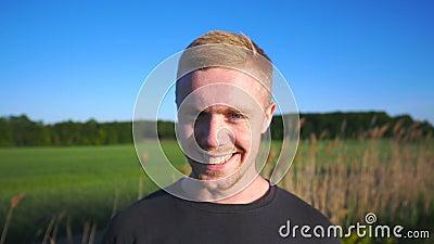 Πορτρέτο του νέου χαμογελώντας ατόμου που στέκεται στο αγροτικό περιβάλλον Όμορφος τύπος με τη γενειάδα που εξετάζει τη κάμερα με απόθεμα βίντεο