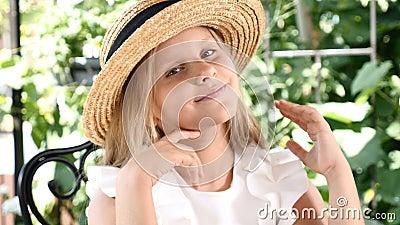 Πορτρέτο του ξανθού ελκυστικού χαμόγελου κοριτσιών, σχετικά με την τρίχα της με ένα καπέλο αχύρου επάνω lifestyle έννοια παιδικής απόθεμα βίντεο