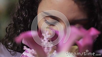 Πορτρέτο του χαρούμενου θηλυκού που μυρίζει τη floral ανθοδέσμη φιλμ μικρού μήκους