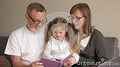Πορτρέτο των χαριτωμένων παππούδων με το εγγόνι τους να διαβάζουν ενδιαφέρουσα ιστορία από το βιβλίο μαζί ενώ κάθονται στο φιλμ μικρού μήκους