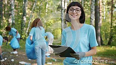 Πορτραίτο νεαρής φιλικής προς το περιβάλλον κυρίας που κάνει γραφειοκρατικές διατυπώσεις κατά τη διάρκεια του καθαρισμού των δασώ φιλμ μικρού μήκους