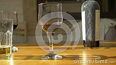 Ποτήρια από ημιτελές κρασί και βότκα σε άδειο τραπέζι μετά την γιορτή απόθεμα βίντεο