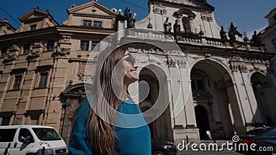 Πράγα, 15 Μαΐου 2019: Ένα χαριτωμένο νεαρό χαμογελαστό κορίτσι με γυαλιά ηλίου κοιτάζει γύρω από τα ιστορικά τσεχικά κτίρια στην  φιλμ μικρού μήκους