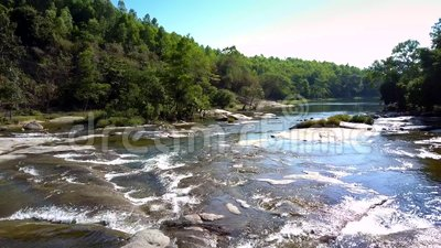 Ρηχός ποταμός με τις ροές αντανάκλασης ηλιοφάνειας ενάντια στη ζούγκλα απόθεμα βίντεο