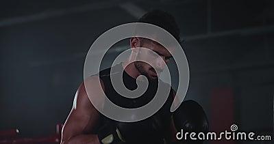 Σε ένα σκοτεινό μάθημα γυμναστικής, ο βαρύς ιδρωμένος τύπος με μεγάλους δικέφαλους που κάνει τις σκληρές ασκήσεις του πυγμαχίας κ απόθεμα βίντεο