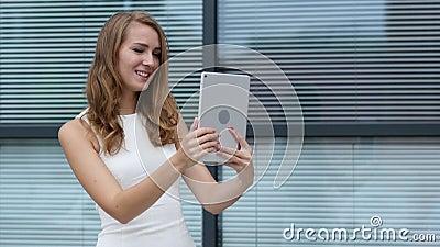 Σε απευθείας σύνδεση τηλεοπτική συνομιλία στην ταμπλέτα από το όμορφο κορίτσι, έξω από το γραφείο απόθεμα βίντεο
