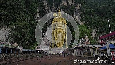 Σε αργή κίνηση συνδετήρας των πετώντας περιστεριών στο πρώτο πλάνο και το χρυσό άγαλμα Murugan ενάντια στον τοίχο βράχου, Gombak, φιλμ μικρού μήκους
