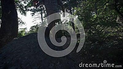 ΣΕ ΑΡΓΗ ΚΊΝΗΣΗ, ΚΛΕΙΣΤΕ ΕΠΑΝΩ: Unrecognizable θαρραλέος αρσενικός οδοιπόρος που αναρριχείται mountaintop, περπατώντας από το ίχνο φιλμ μικρού μήκους