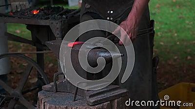 Σιδηρουργείο, αρσενικά χέρια με σφυρί σφυρηλατώντας μια καρδιά από σίδηρο απόθεμα βίντεο