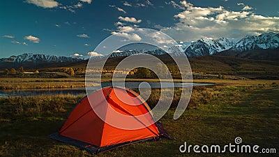 Σκηνή τουριστών στο στρατόπεδο μεταξύ των αλπικών λιβαδιών στα βουνά στο ηλιοβασίλεμα απόθεμα βίντεο