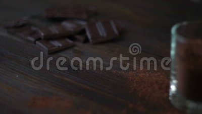 σκοτάδι σοκολάτας ράβδων Σκόνη κακάου στο φλυτζάνι γυαλιού στο ξύλινο υπόβαθρο απόθεμα βίντεο