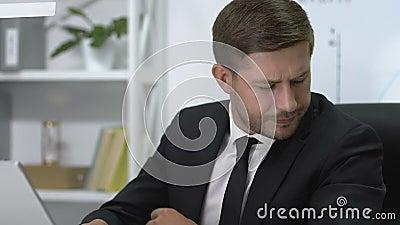 Σοβαρός άνδρας διευθυντής που εργάζεται στο φορητό υπολογιστή και ξαφνικά νιώθει οξύ πόνο στον ώμο απόθεμα βίντεο