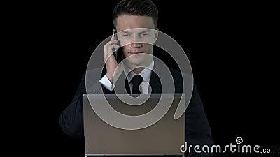 Σοβαρός επιχειρηματίας στη δακτυλογράφηση κοστουμιών στο lap-top, που απαντά στο τηλέφωνο, επίδραση μεταλλινών απόθεμα βίντεο