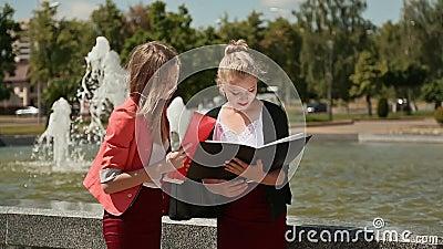 Σπουδαστές νέων κοριτσιών του κολλεγίου μαζί στο πάρκο κοντά στην πηγή Ο ήλιος λάμπει φιλμ μικρού μήκους
